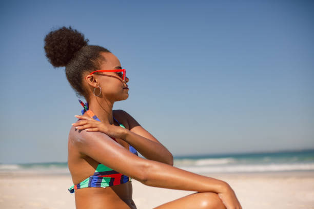 Woman in bikini applying sunscreen lotion on shoulder at beach in the sunshine Side view of African american woman in bikini applying sunscreen lotion on shoulder at beach in the sunshine suntan lotion stock pictures, royalty-free photos & images