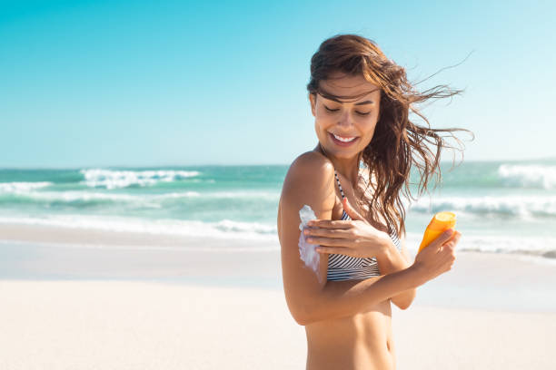 Woman in bikini applying sunscreen stock photo