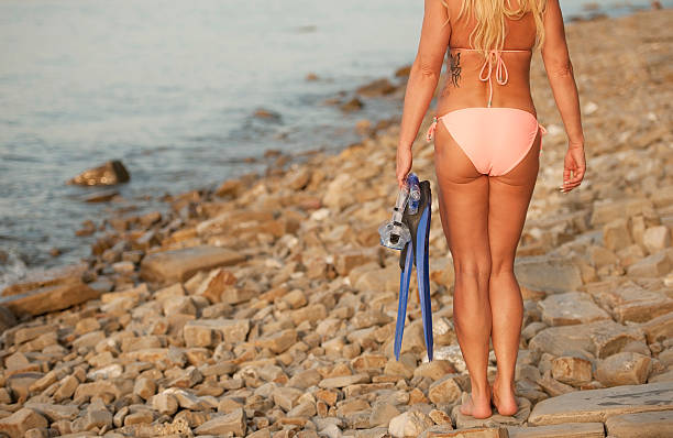 Woman in bikini holding snorking flippers Beautiful adult woman in pink bikini holding snorking flippers. Back view. Horizontal color image. Piran, Slovenia, Europe. middle aged women in bikinis stock pictures, royalty-free photos & images