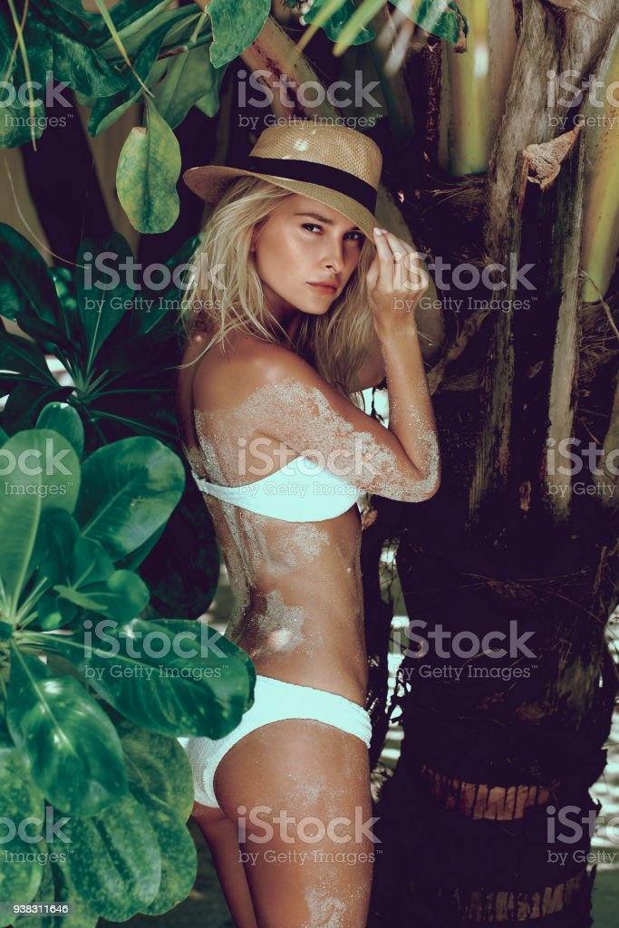 Woman in bikini on a tropical beach with palm trees. stock photo