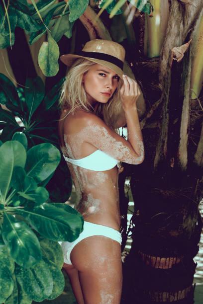 Woman in bikini on a tropical beach with palm trees. stock photo