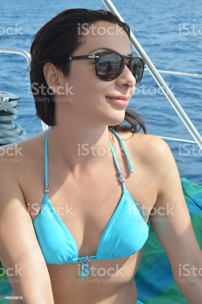 Woman in bikini posing on a yacht with sunglasses stock photo