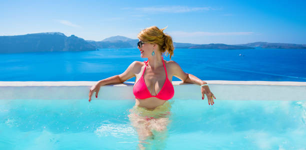 woman in bikini relaxing in luxury outdoor pool - older women bikini stock pictures, royalty-free photos & images
