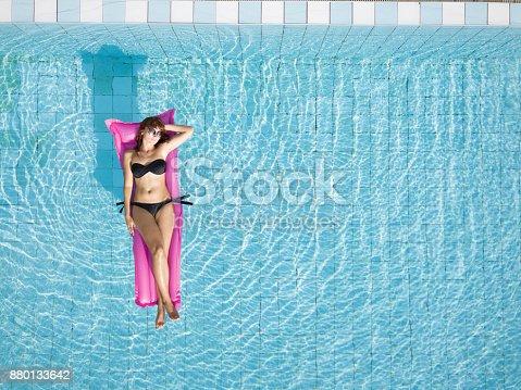 istock woman in bikini relaxing on inflatable mattress in the swimming pool 880133642