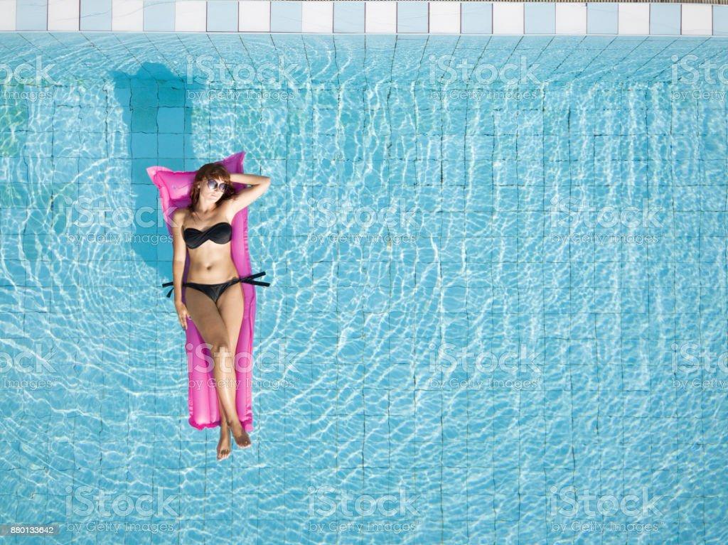 Frau im Bikini auf Luftmatratze im Pool entspannen – Foto