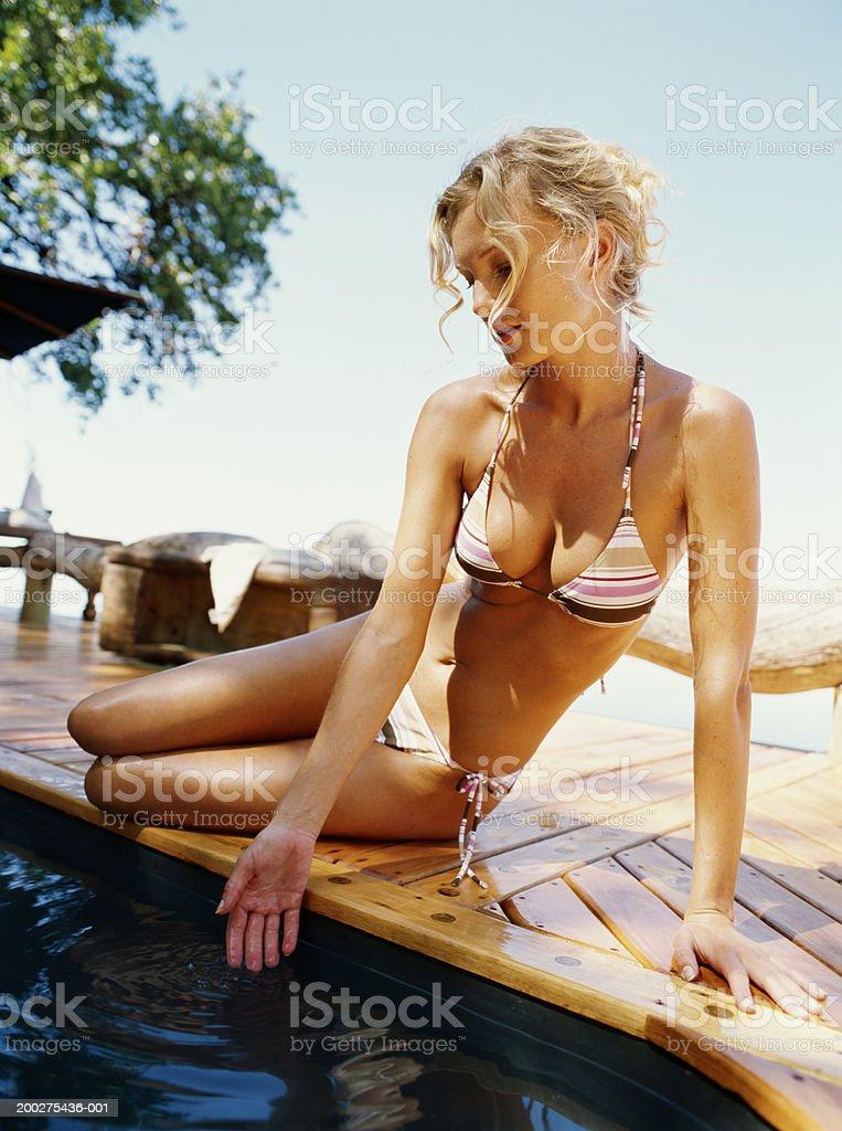 Woman in bikini sitting by pool, dipping hand in water royalty-free stock photo