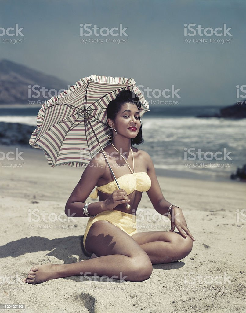 Woman in bikini sitting on beach holding umbrella, smiling, portrait stock photo