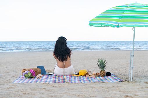 Woman in bikini sitting on the beach in summer.