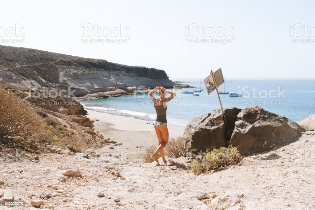 Woman in bikini standing above bay and ocean - fotografia de stock