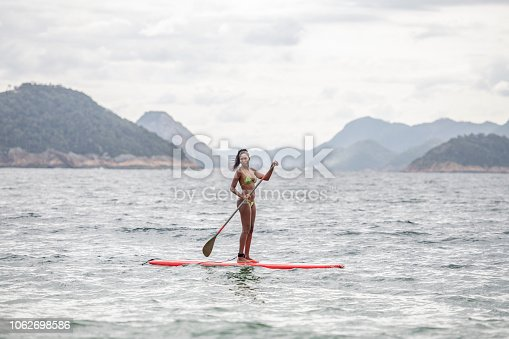 Young woman in swimwear with oar, on surf board in water, views of Rio de Janeiro mountains in background