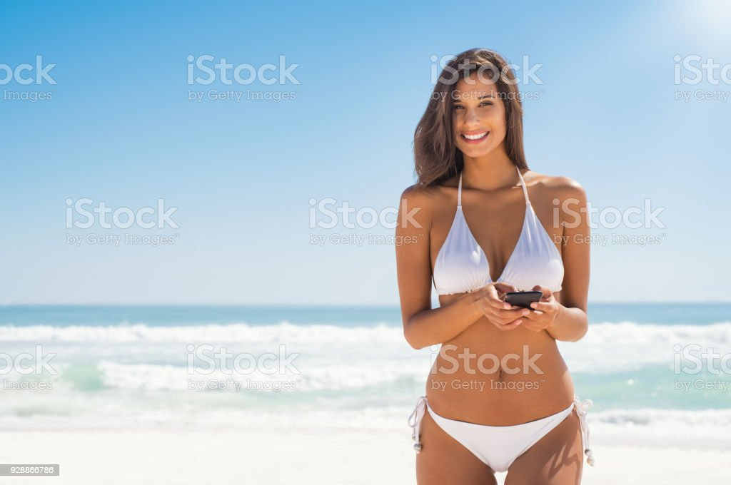 Woman in bikini using phone foto stock royalty-free
