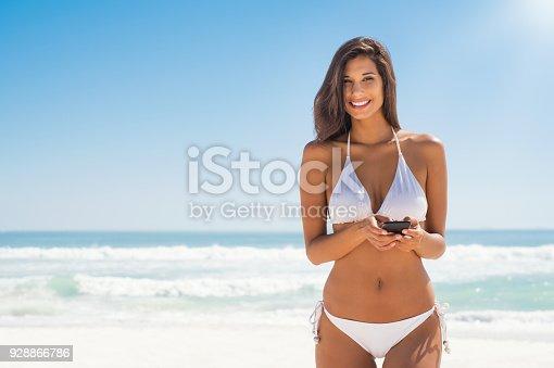 istock Woman in bikini using phone 928866786