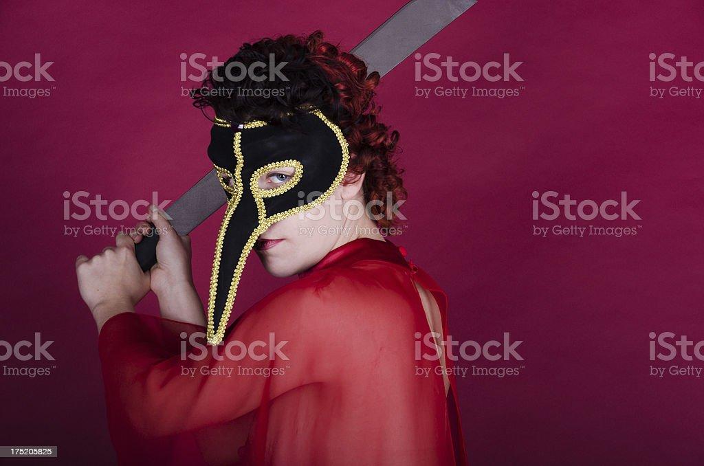 Woman in bird mask wielding a machette. stock photo
