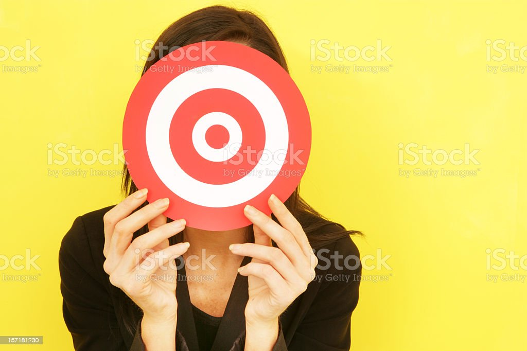 A woman in black against a yellow backdrop holding a target royalty-free stock photo