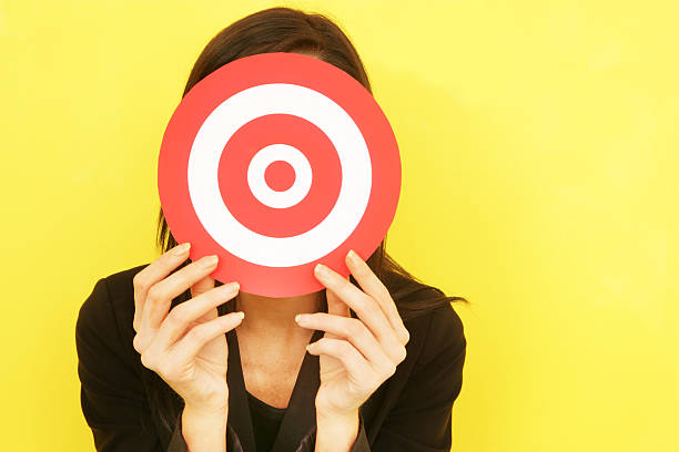 A woman in black against a yellow backdrop holding a target stock photo