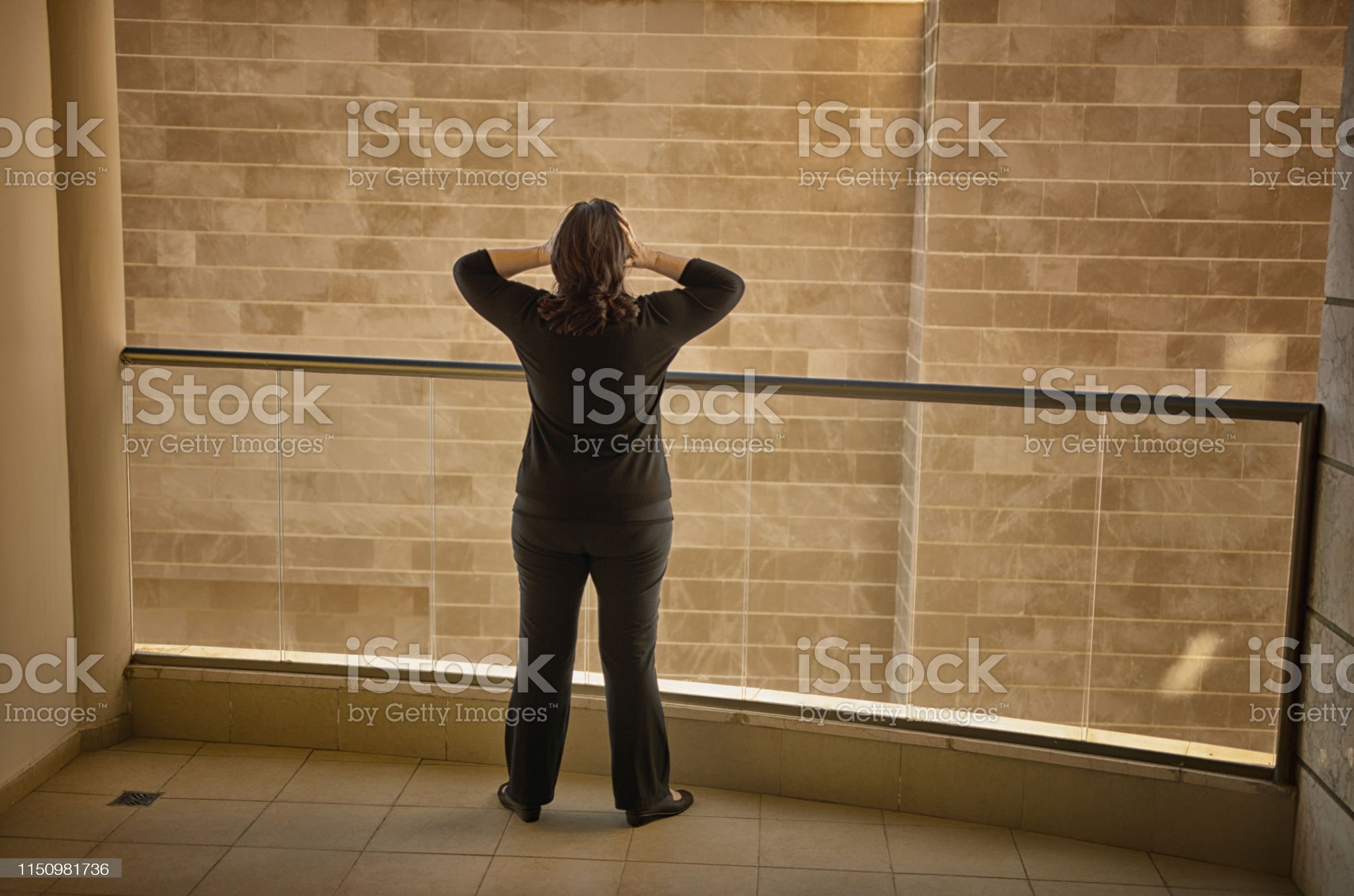 Small mature adult woman stands near exterior decorative glass balcony aluminum fence looking at the wall