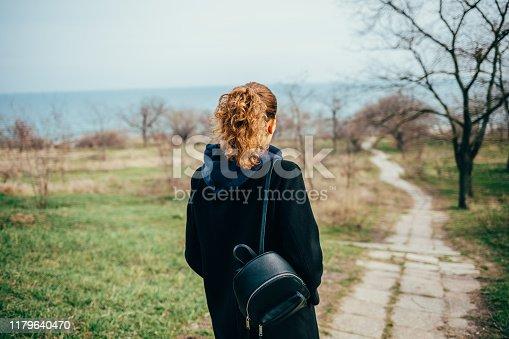 Woman in black coat walking along the sea