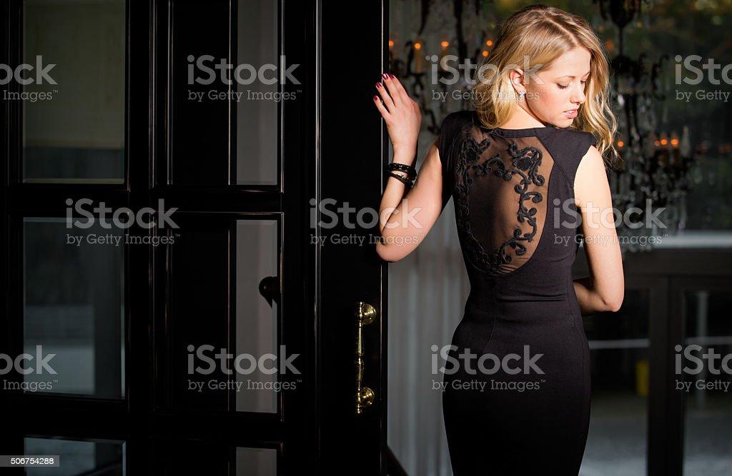 Woman in black dress looking over her shoulder stock photo
