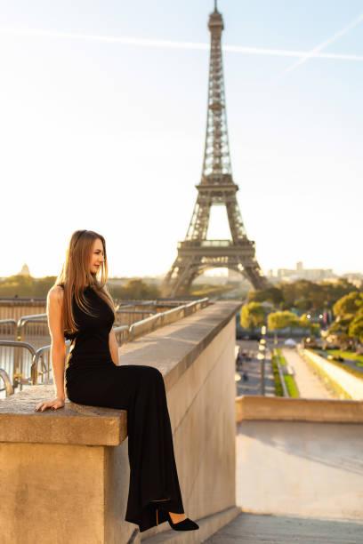 frau im schwarzen kleid in der nähe des eiffelturms. fashion week in paris - hochzeitsreise 1 woche stock-fotos und bilder