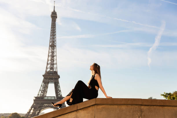 frau im schwarzen kleid in der nähe des eiffelturms. pariser mode - hochzeitsreise 1 woche stock-fotos und bilder