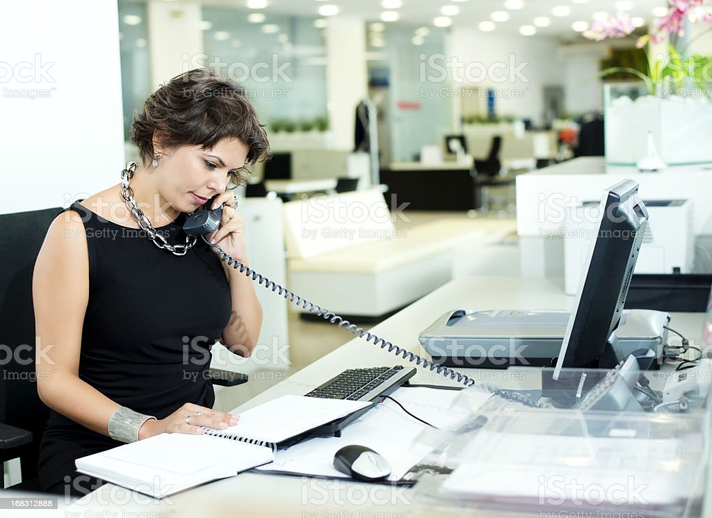 Woman in black dress speaking on phone on office stock photo