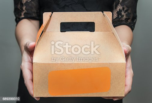 istock A woman in black dress stood bringing a snack box 689399310