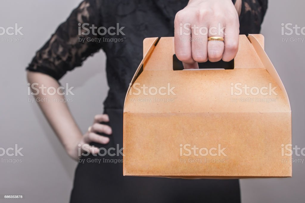 A woman in black dress stood with arms akimbo and bringing a snack box stock photo