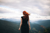 Young Caucasian Woman in black dress walking in the mountains and looking at view