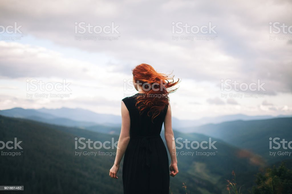Woman in black dress walking in the mountains and looking at view stock photo