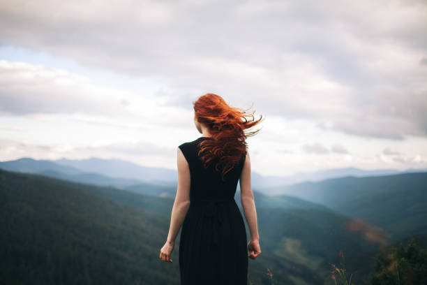 woman in black dress walking in the mountains and looking at view - rear view stock photos and pictures
