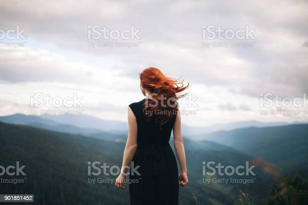 Photo of Woman in black dress walking in the mountains and looking at view