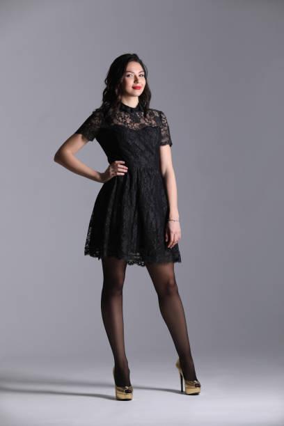 Woman in black dressin studio. Gray background. Photographie retouchee stock photo