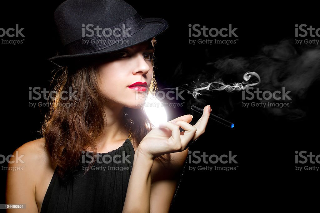 Woman in black hat posing with thin electronic cigarette female vaping an electronic cigarette as a healthy alternative 2015 Stock Photo