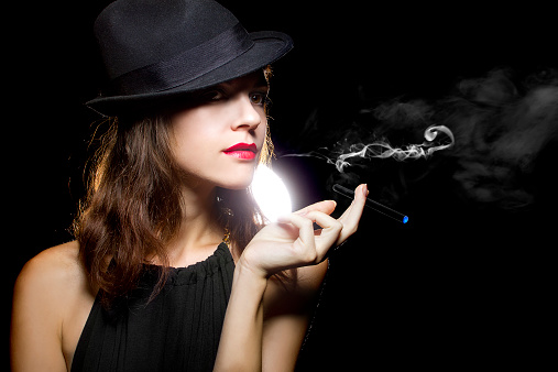 Woman In Black Hat Posing With Thin Electronic Cigarette Stock Photo - Download Image Now