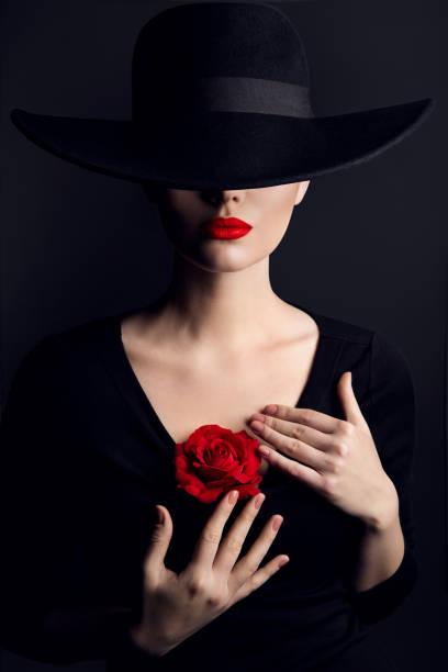 Woman in Black Hat Rose Flower, Elegant Fashion Model Luxury Beauty Portrait on Black, Red Lips and Hidden Eyes stock photo