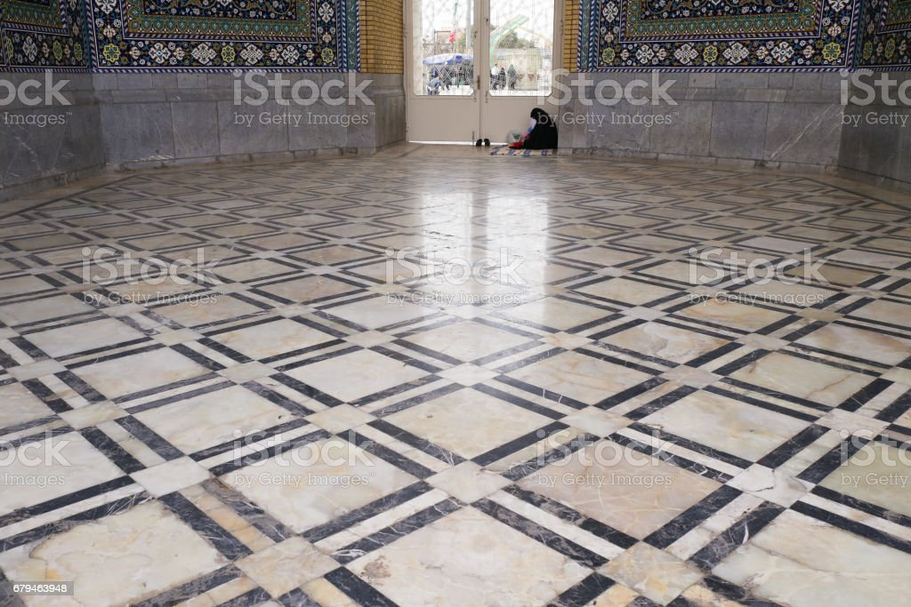 Woman in black hijab siting on the nice squares texture ground in a mosque in Qom, Iran royalty-free stock photo