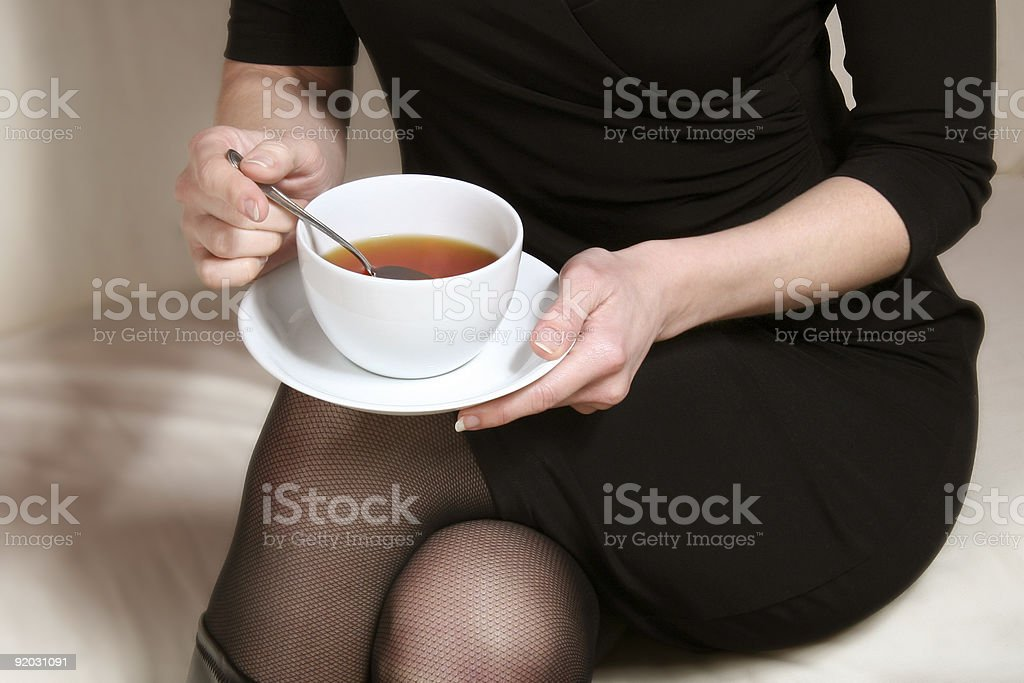 woman in black holding a cup of tea at hands royalty-free stock photo
