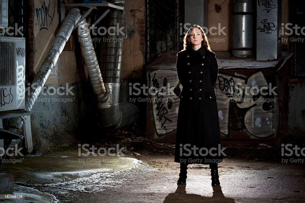 Woman in black overcoat standing on back street stock photo