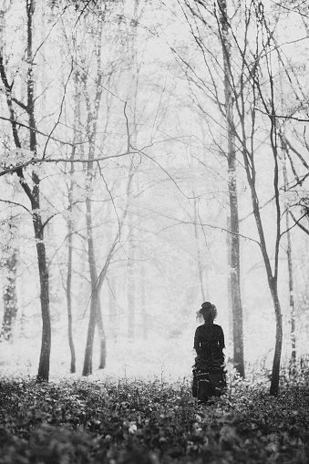 Black and white image of woman in a black victorian dress in a misty late autumn forest.