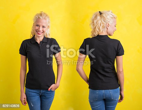 istock Woman in black polo T-shirt on yellow background 629143826