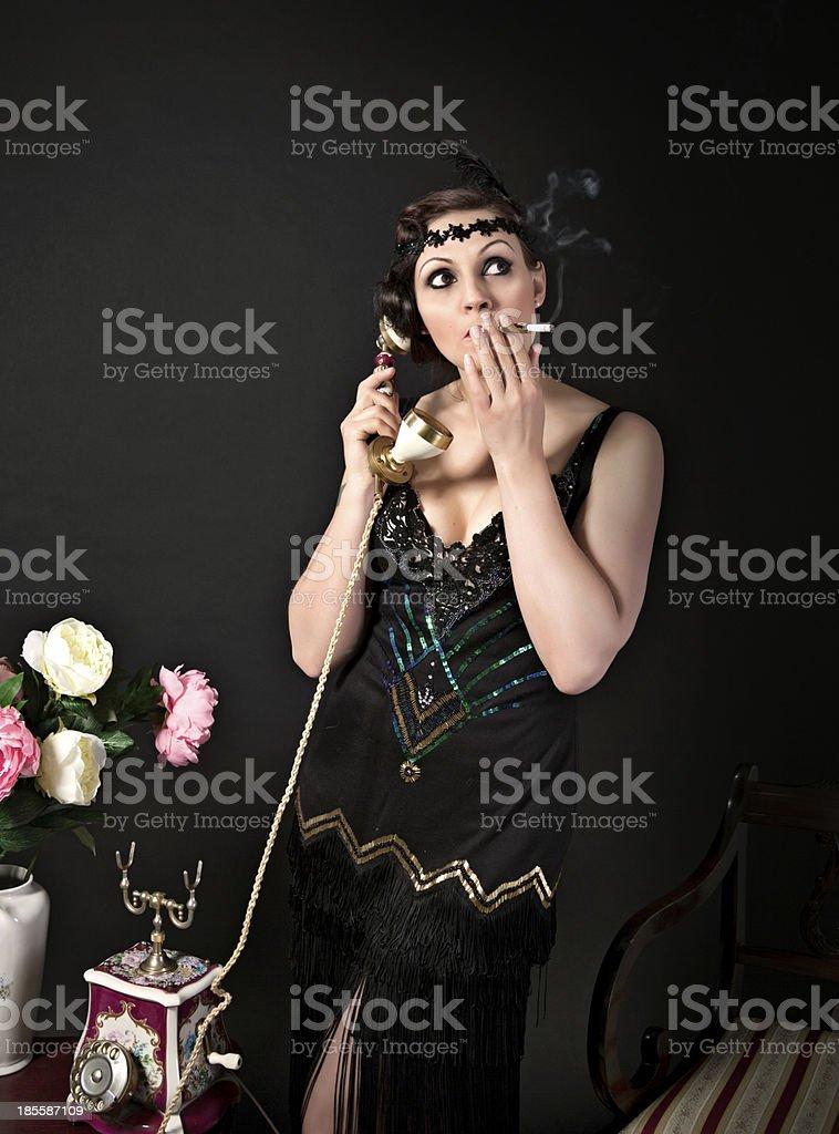 Woman in black retro dress smokes while talking on phone stock photo