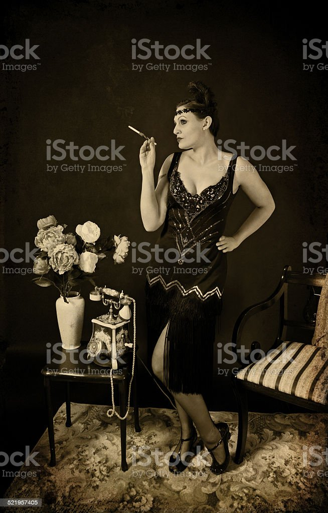 Woman in black retro dress with cigarette in the holder stock photo