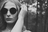 Woman in black round sunglasses in black and white