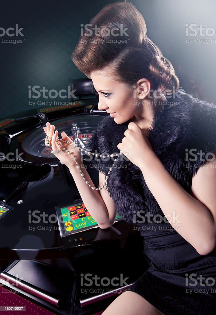 woman in  black  sitting at  roulette table. royalty-free stock photo