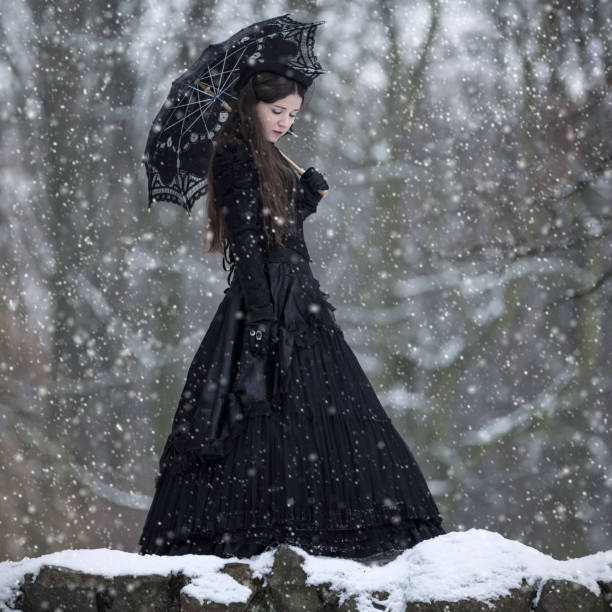 woman in black victorian dress in the winter park - viktorianischer stil stock-fotos und bilder