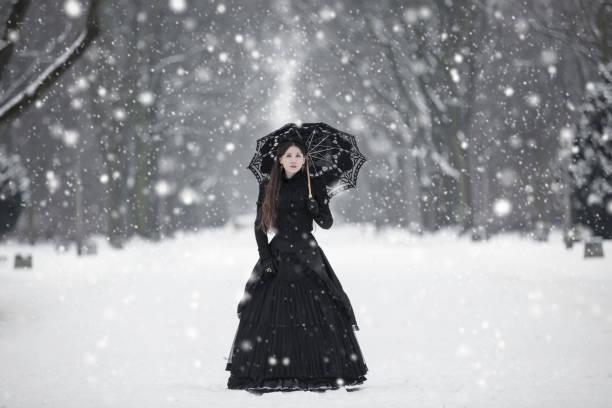 frau in schwarz viktorianischen kleid im winter park - gothic kleid stock-fotos und bilder