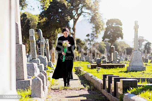 A bereaved young woman, wearing black and carrying flowers, walks through memorial stones in  a cemetery.