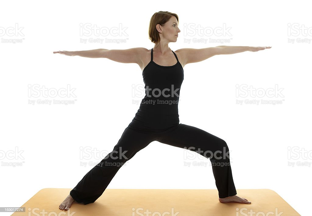 A woman in black workout attire does a yoga pose royalty-free stock photo