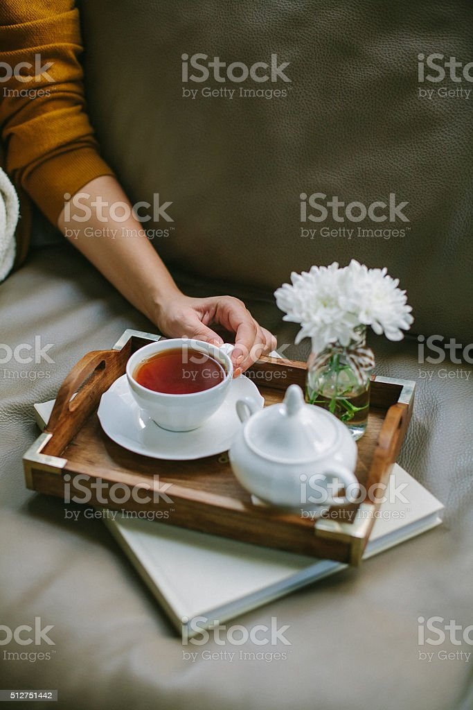 Woman in yellow drinks tea and reads book
