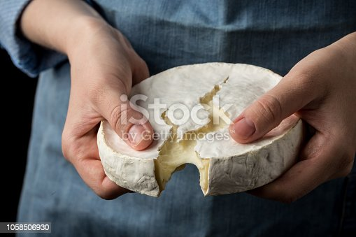 Woman in blue apron holding soft french camembert cheese on dark background. Studio shot
